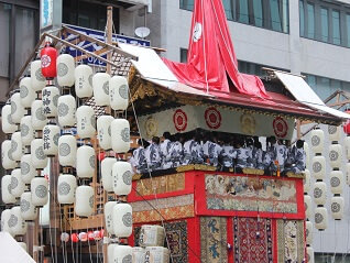 Photo of Kyoto Gion Festival Float with white lanterns. People wearing Yukata are sitting on the top of the float.